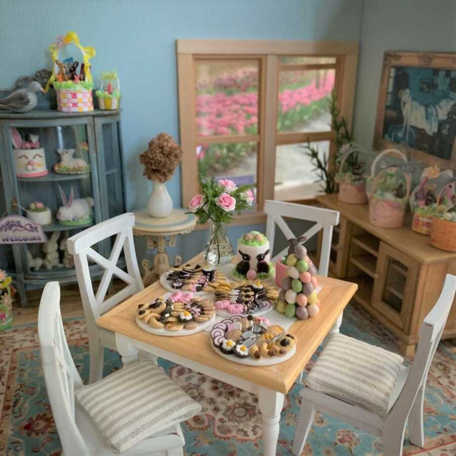 Miniature Easter dollhouse scene featuring clay sculpted cookies and cakes.