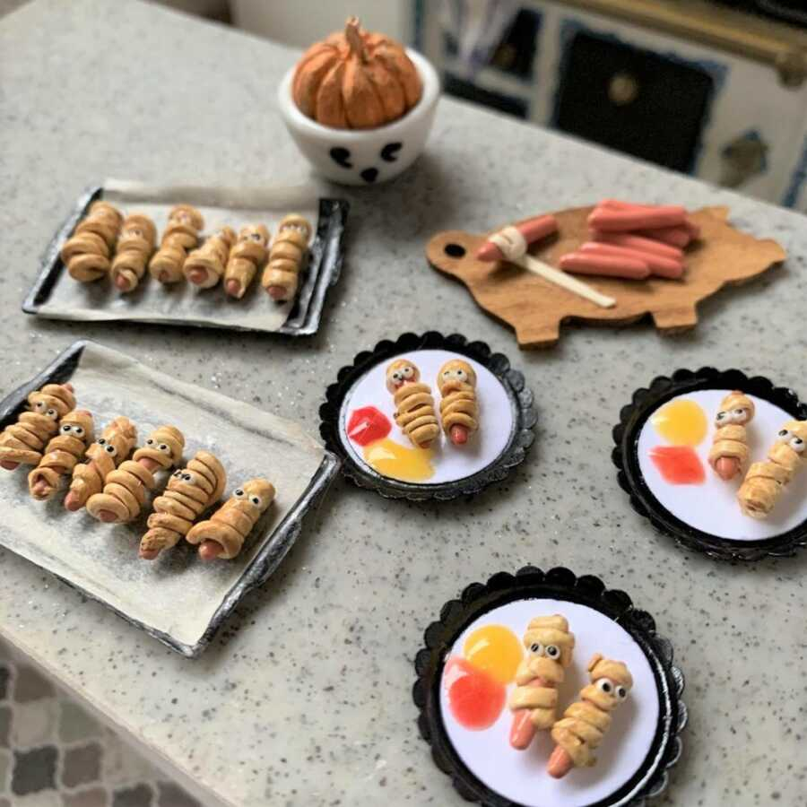 Miniature Halloween mummy hot dogs made from sculpted clay.
