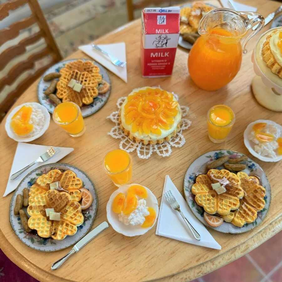 Miniature breakfast waffles and orange juice made from sculpted clay.