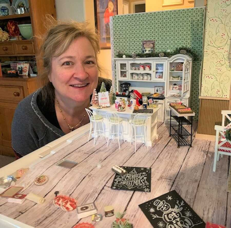 Dianne pictured with one of her miniature dollhouse scenes, decorated for Christmas.