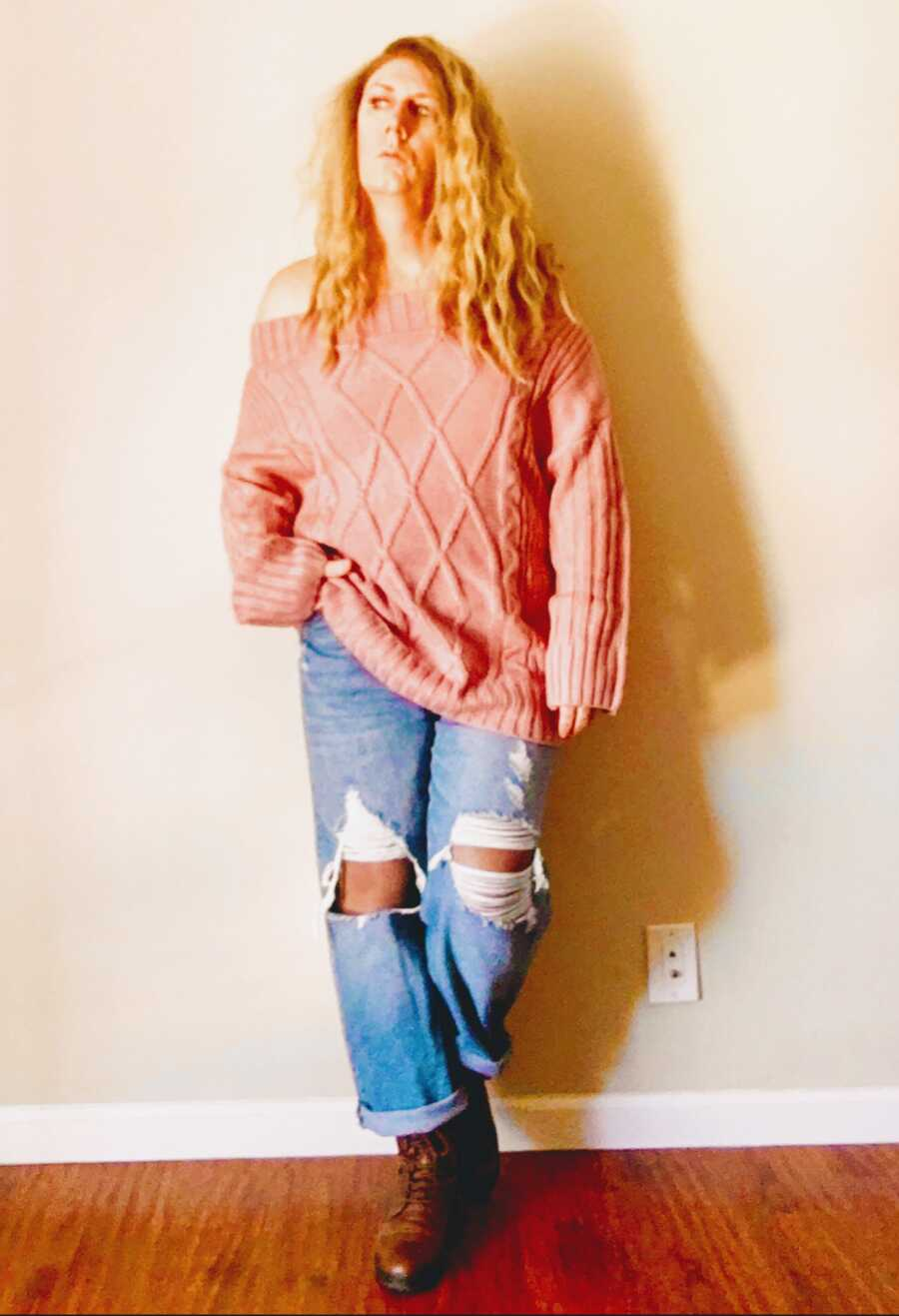 trans woman wearing a pink shirt and ripped jeans