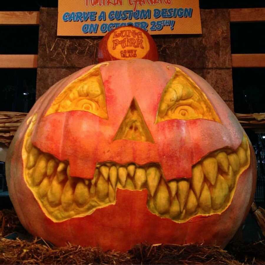 Giant pumpkin sculpture of a Jack-O-Lantern face at Luna Park contest, created by Maniac Pumpkin Carvers.