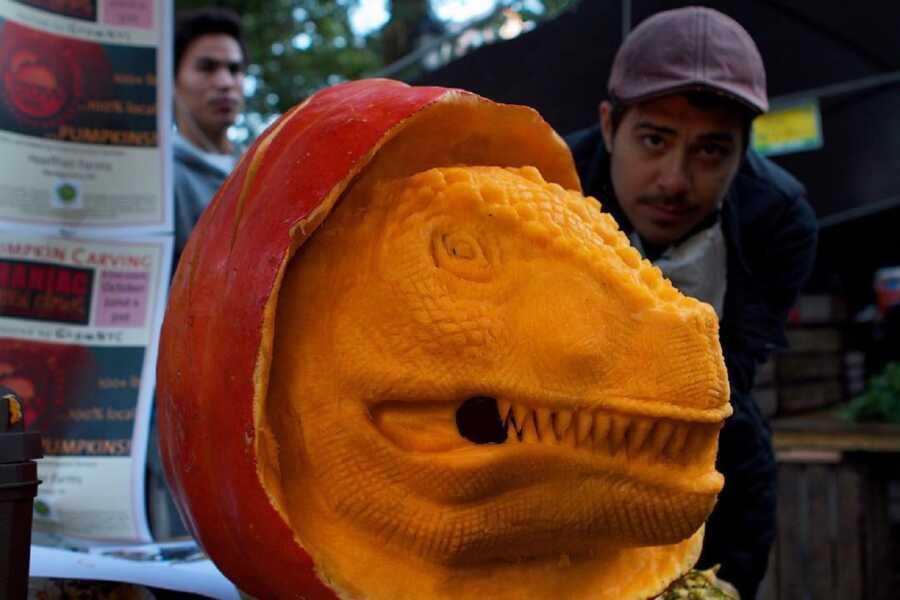 Large pumpkin sculpting of a dinosaur head, created by Maniac Pumpkin Carvers.