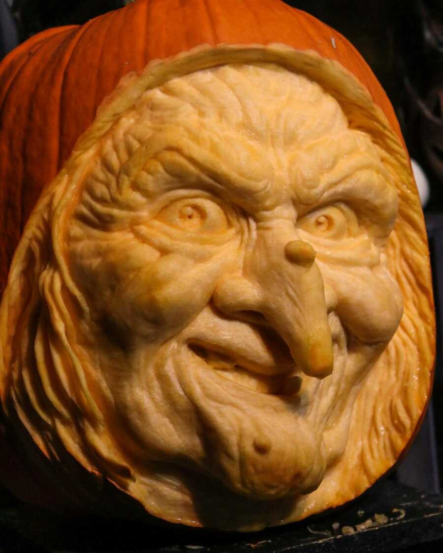 Pumpkin sculpture of a witch's face, created by Maniac Pumpkin Carvers.