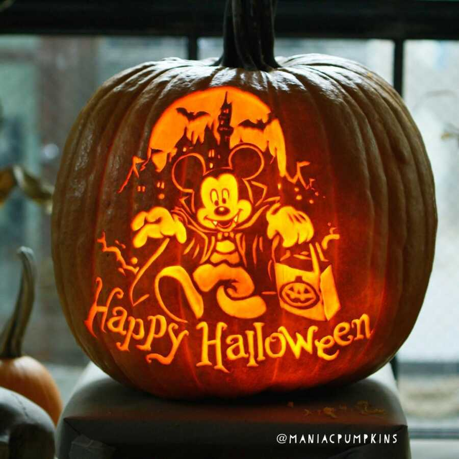 Pumpkin carving of vampire Mickey Mouse and haunted castle, created by Maniac Pumpkin Carvers.