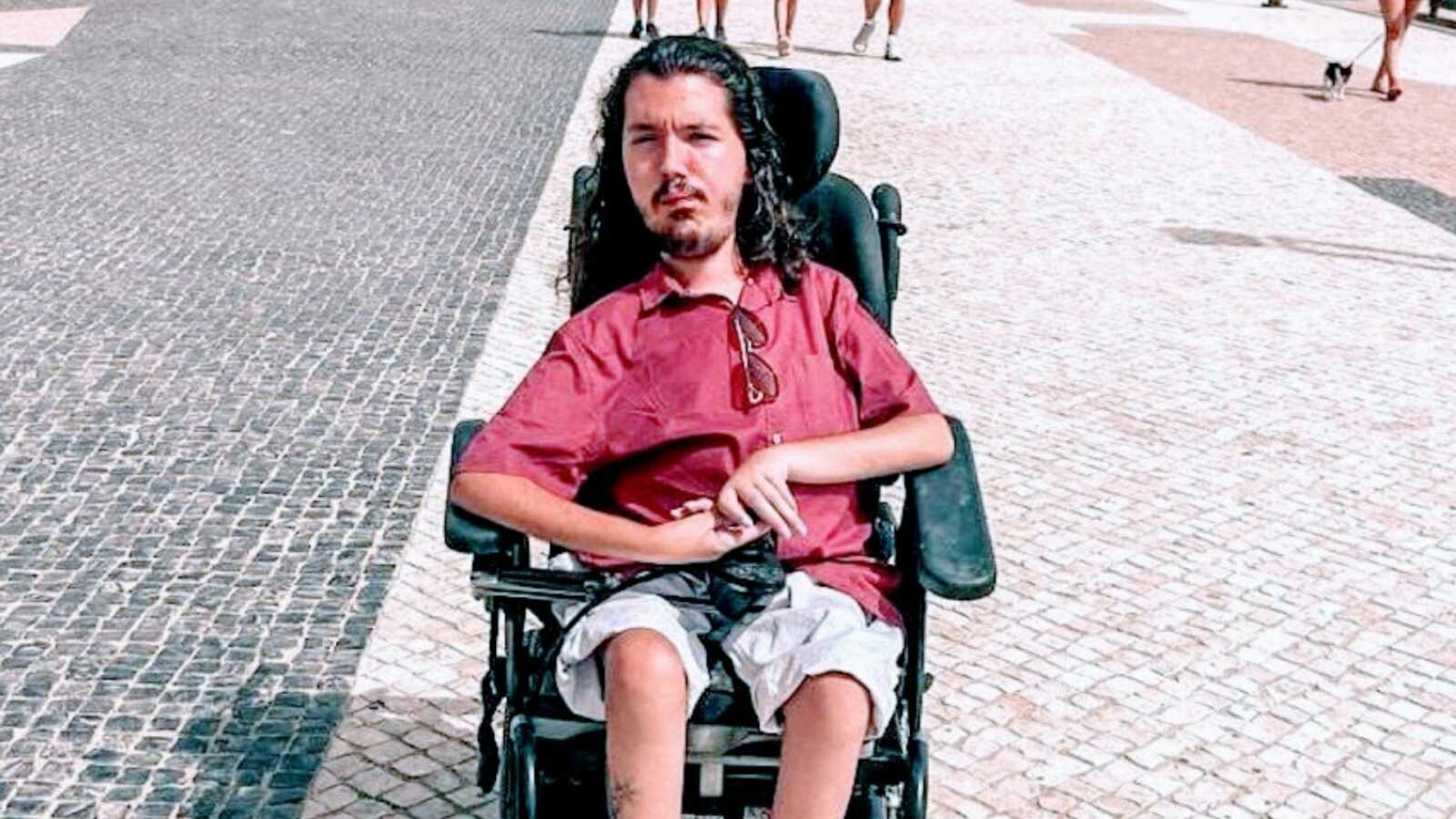 A man with spinal muscular atrophy sits in a wheelchair