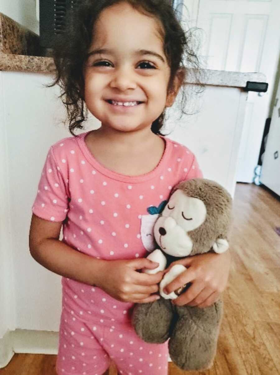 moms' daughter holding a toy she is about to give