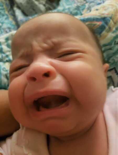 Baby crying because mom burped while feeding them.