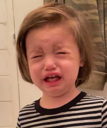 Toddler throwing a tantrum because he couldn't dip his toothbrush in the toilet.