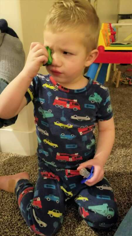 Toddler throwing a tantrum because he couldn't glue toy food to his eyes.