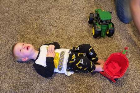 Toddler throwing a tantrum because Santa brought the wrong tractor.