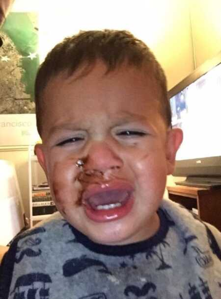Toddler throwing a tantrum because he couldn't lick the chocolate off his face.