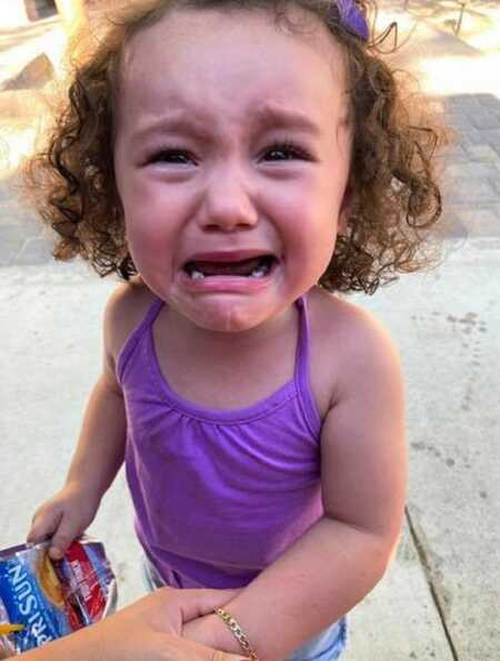 Toddler throwing a tantrum because she bit herself trying to bite someone else.